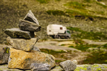 Mountains stone stack and camper car on national tourist scenic route Gamle Strynefjellsvegen. Travel in motor home and adventure.