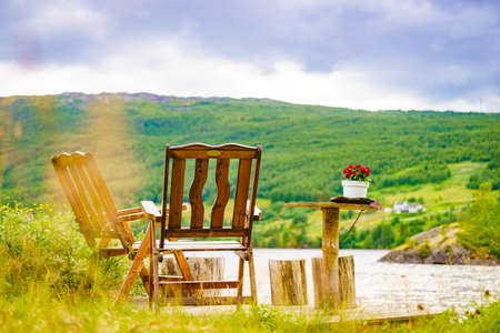 Picnic site rest stop area wooden table with flowers decoration and chairs on norwegian lake fjord shore. Holidays relaxation on trip. Scandinavia Europe.