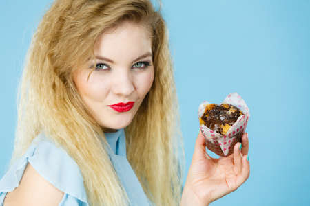 Sweet food sugar make us happy. Attractive blonde woman holds yummy chocolate cupcake in hand, craving for cake. Appetite and tasty meal dessert.