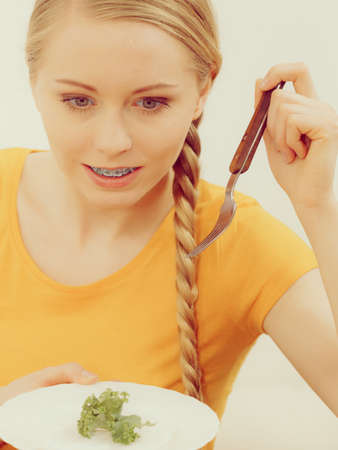 Happy young woman about to eat lettuce holding fork and smiling. Toned image colors. Stock Photo