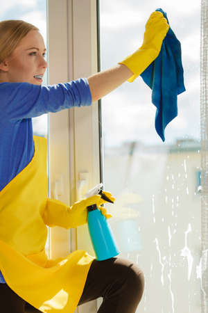 Young woman in yellow gloves cleaning window with blue rag and spray detergent. Spring cleanup, housework concept