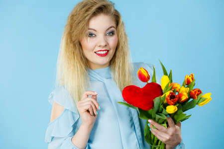 International women or valentine day. Beautiful woman blonde hair fashion make up holding tulips bunch and red heart sign. On blue Standard-Bild - 133967174