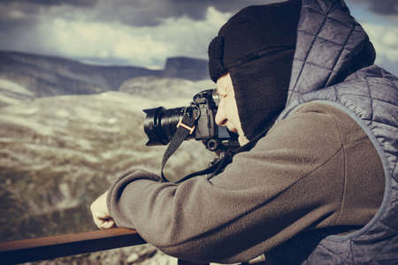 Male tourist taking photo with camera, enjoying mountains landscape from Dalsnibba area Geiranger Skywalk viewing platform, Norway. Фото со стока