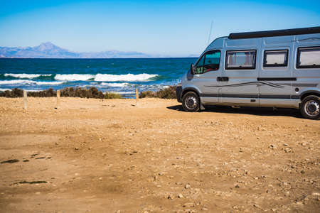 Camper van recreational vehicle on mediterranean coast in Spain. Camping on nature beach. Holidays and travel in motor home.