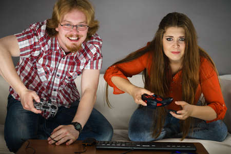 Addicted couple playing video games together being very emotional. Studio shot