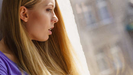 Shocked young blonde teenage woman looking through window seeing something horrible outside.