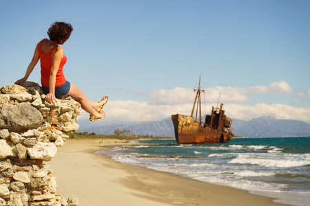 Travel freedom. Mature tourist woman on beach enjoying summer vacation. An old abandoned shipwreck, wrecked boat in the background Zdjęcie Seryjne