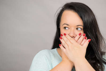 Shocked surprised plus size adult woman covering her mouth with hand, being terrified or scared. Female seeing something shocking and speechless.