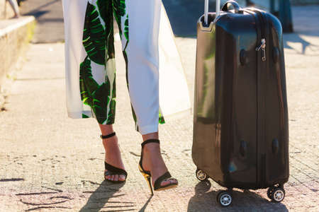 Unrecognizable woman arriving to new city wearing long dress and high heels, holding her suitcase on wheels.