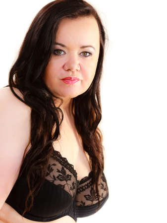 Plus size fat mature woman wearing black lace bra showing her big chest breasts, on white. Bosom, brafitting and underwear concept.