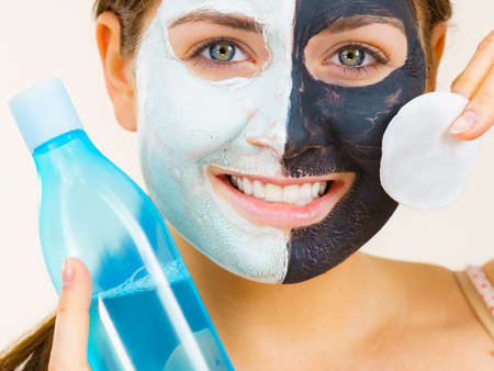 Woman with clay carbo black mask on one half face and white mud on second half. Girl removing cosmetic scrab with cotton swab. Female taking care of oily complexion. Skincare. Stock fotó