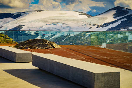 Fantastic view on mountains landscape from Dalsnibba viewpoint, Geiranger Skywalk platform floor surface and rest benches, Norway.
