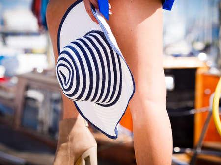 Woman beautiful slim legs wearing suede beige high heels shoes holding sun hat