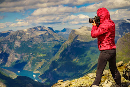 Tourism vacation and travel. Female tourist taking photo with camera, enjoying Geiranger fjord and mountains landscape from Dalsnibba Plateau viewpoint at windy day, Norway . Zdjęcie Seryjne