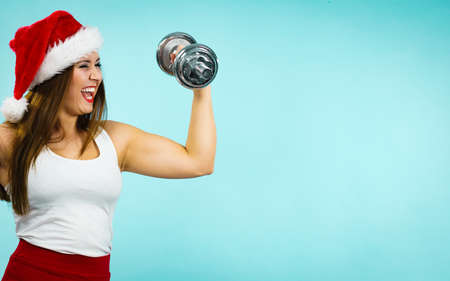 New Year fitness and building muscles resolution. Woman in santa claus hat lifting dumbbells weights, on blue. Goal achievement in training.
