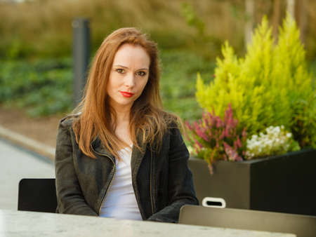 Beautiful woman sitting in urban park relaxing place wearing black jeans jacket. Female fashion model during spring weather, having long brown hair wind tousled. Zdjęcie Seryjne