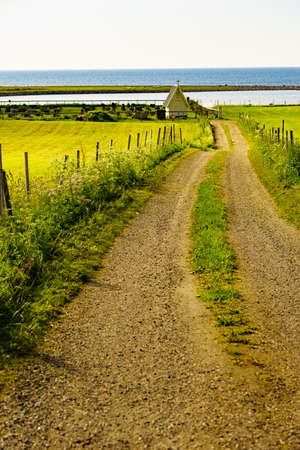 Country road to cemetery burial site with chapel on seaside, Andoya island, Norway.