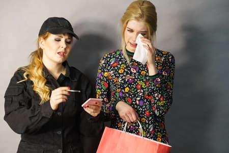 Ladendiebstahl ist ein Verbrechen. Teenager-Mädchen beim Diebstahl von Kleidung von weiblichen Wachmann erwischt Kundendieb