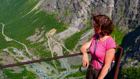 Tourist woman on Trollstigen viewpoint. Trolls Path or Trollstigveien mountain road in Norway. National route. Touristic attraction. Zdjęcie Seryjne