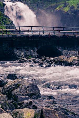 Norwegian landscape. Waterfall Latefoss Latefossen with stone arched bridge road, Odda Hordaland Norway. National tourist Hardanger road 13.