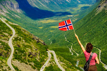 Tourist woman with norwegian flag on Trollstigen viewpoint. Trolls Path mountain road in Norway. National route. Touristic attraction. Zdjęcie Seryjne
