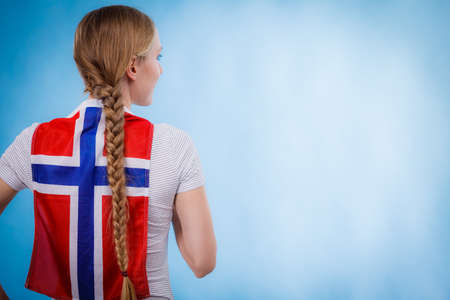 Blonde girl braid hair with norwegian flag on her back, copy space text area. Scandinavian people.