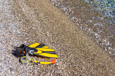 Snorkel equipment flippers and snorkeling mask tube lying on stone beach sea shore. Summer vacation swimming fun concept. Reklamní fotografie