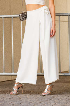 Unrecognizable woman wearing fashionable outfit. Close up at silver high heels, white culottes trousers and small black bag purse with pearls Stock Photo