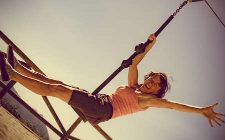 Adult freedom woman having fun on zipline, descend on rope, cable aerial ropeslide. Happiness and carefree.
