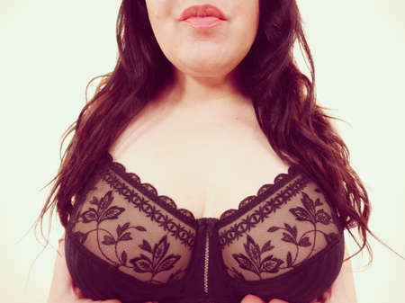 Close up female big breast in lingerie, wide angle view. Plus size fat woman wearing black lace soft bra. Bosom, brafitting and underwear concept.
