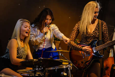 Woman singing while rest of the band playing instruments, performing on stage. Female musicians: guitarist, drummer and singer