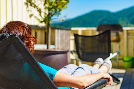 Entspannen Sie in der Sonne. Entspannung der erwachsenen Frau im Liegestuhl im Freien auf der Veranda. Ferienhaus.