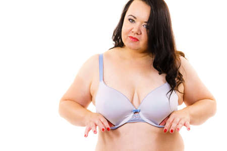 Plus size fat mature woman wearing bra, on white. Female breast in lingerie. Bosom, brafitting and underwear concept.