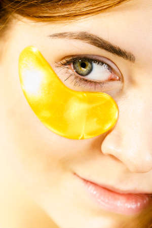 Woman applying golden collagen patches under eyes. Mask removing wrinkles and dark circles. Female taking care of delicate skin around eye. Beauty treatment. Standard-Bild