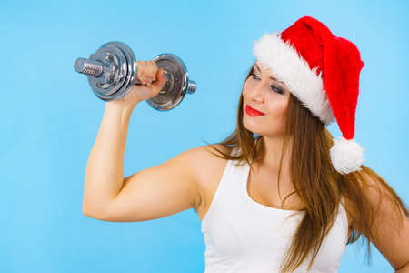 New Year fitness and building muscles resolution. Woman in santa hat lifting dumbbells weights, on blue. Goal achievement in training. Imagens