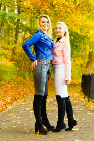 Two friends women wearing fashionable outfit. Female having navy bue pink leather jacket, jeans and high ankle black boots.
