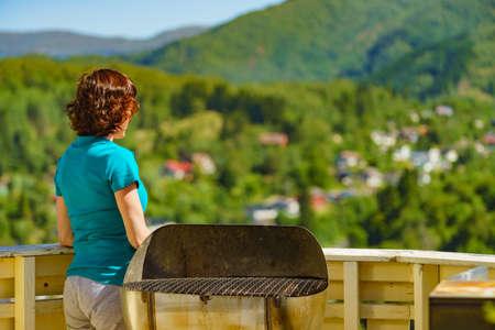 Woman standing on veranda enjoying summer landscape with stunning view of Osteroy island in Norway Standard-Bild