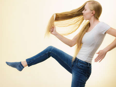 Blonde woman with brush combing her very long hair. Teenage girl taking care refreshing her hairstyle. Haircare concept.