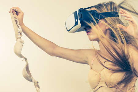 Long hair blonde woman wearing bra and virtual reality goggles headset, vr box. Female holds lingerie in hand. Bosom, brafitting and underwear concept.