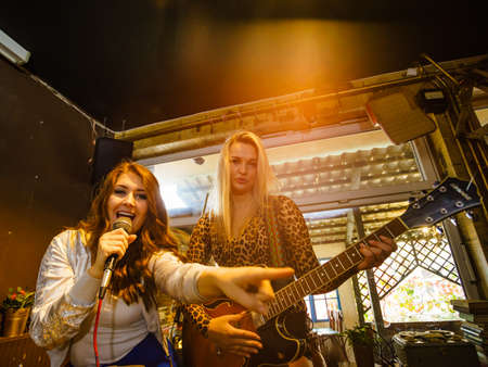Woman singing while rest of the band playing instruments, performing on stage. Female musicians: guitarist and singer
