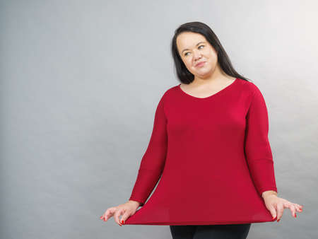 Curvy big woman covering her hips belly with plus size cotton elastic top tunic. 免版税图像