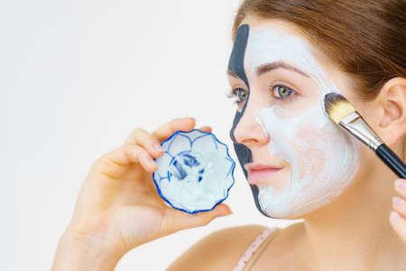 Woman with clay carbo black mask on half face applying white mud to clean skin. Girl taking care of oily complexion. Beauty procedures. Skincare. Stock fotó