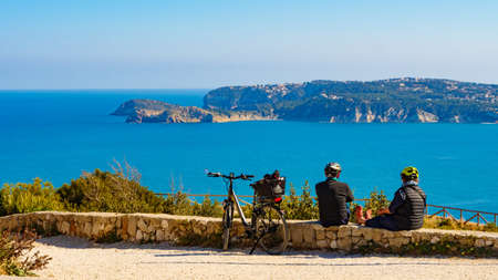 CAPE SAN ANTONIO, SPAIN - MARCH 28, 2019. Couple with bicycle resting on sea coast. Holidays, sport and activity.