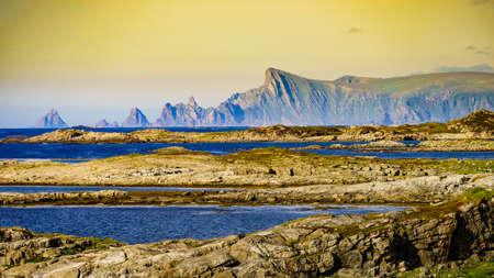 Seascape on Andoya island. Scenic rocky coastline with mountain peaks in distance, view from Bukkekjerka rest stop area, Vesteralen archipelago, Norway.