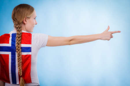 Blonde girl braid hair with norwegian flag on her back, female pointing with finger to copy space text area. Scandinavian people. Foto de archivo