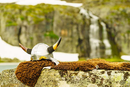 Equipment of viking or barbarian warrior outdoor on nature. Viking helmet on brown fur of animal in Norway. Tourism and traveling concept 版權商用圖片