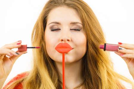 Junge erwachsene Frau, die Lippenstift oder Lipgloss anwendet und ihr Make-up fertig macht, das falsche Lippen auf Stock hält Standard-Bild