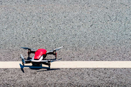 Preparation quadrocopter to start flying, drone starting from asphalt road