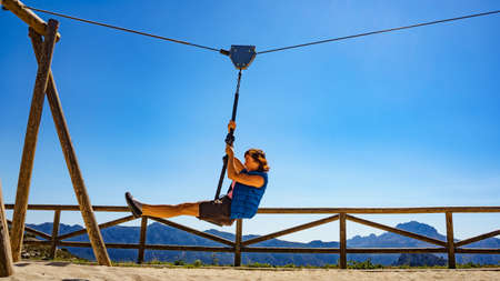 Adult freedom woman tourist having fun on zipline, descend on rope, cable aerial ropeslide. Mountains rest place in Spain Alicante region. Costa Blanca holiday.