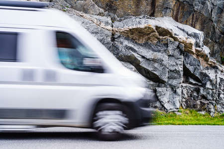 Camper trailer van vehicle car driving in high speed. Blurry shot of motorhome riding fast in mountains. Stock Photo